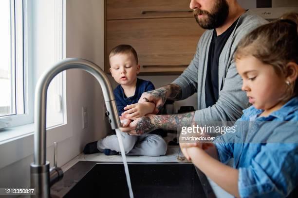 """padre che insegna ai bambini come lavarsi le mani in quarantena isolamento covid-19 - """"martine doucet"""" or martinedoucet foto e immagini stock"""