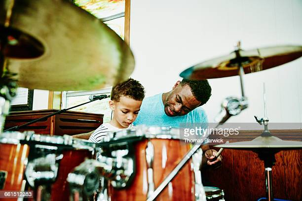 Father teaching young son to play drums