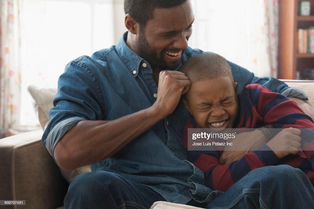 Father teasing son on sofa : Stock Photo