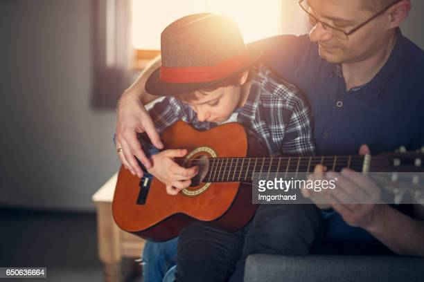 Father teching son to play guitar