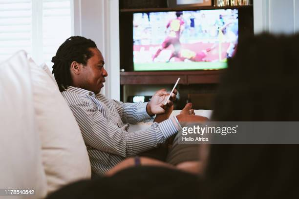father texting whilst mother watches sport on tv - sport stock pictures, royalty-free photos & images