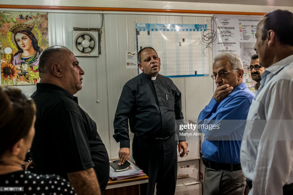 Father Thadet, the Chaldean Catholic priest of Karemles, talks with local residents in the Karemles Complex in Erbil, northern Iraq, on September 8, 2017. The people have been living here for three years since Islamic State militants took the Christian town of Karemles in northern Iraq. They are soon to return to their homes in the town.