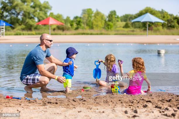 father & three children at beach on summer day - lake auburn stock photos and pictures