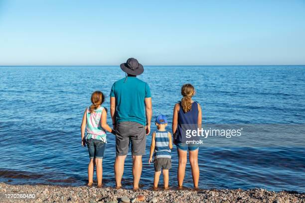 father & three children on rocky beach of lake superior - lake superior stock pictures, royalty-free photos & images
