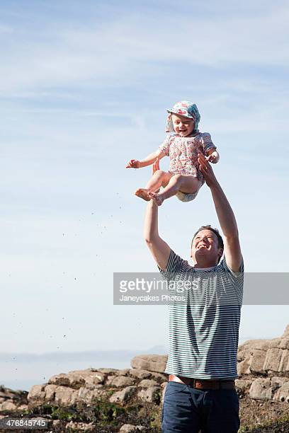 Father throwing child in air on beach
