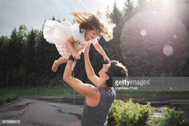 father throwing daughter, rain and sun in forest - gender bender foto e immagini stock