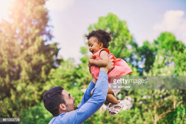 Father throwing his baby daughter in the air in a park