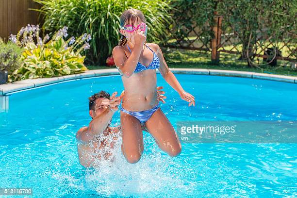 Father throwing his daughter in a pool