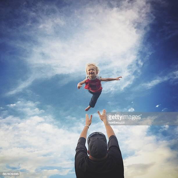 Father throwing his son in the air
