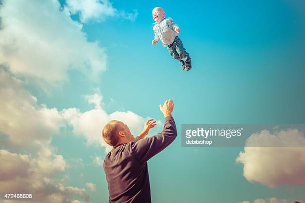 Father throwing son in air ready to catch him