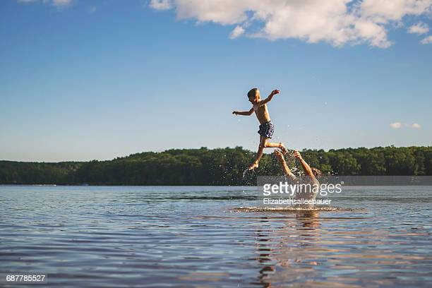 Father throwing son in the air while standing in a lake