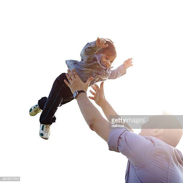 father throwing son into air - throwing stock pictures, royalty-free photos & images