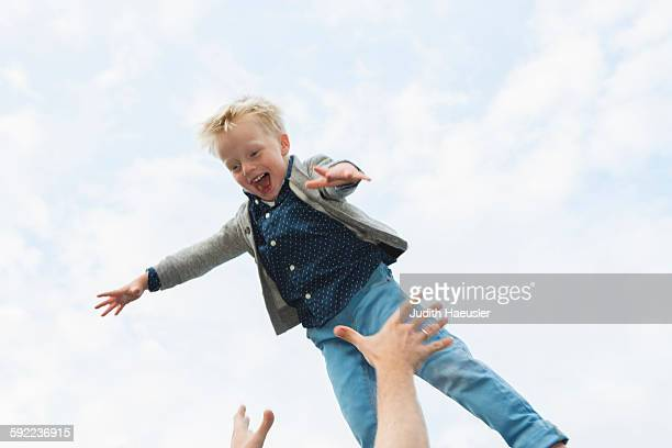 Father throwing son mid air