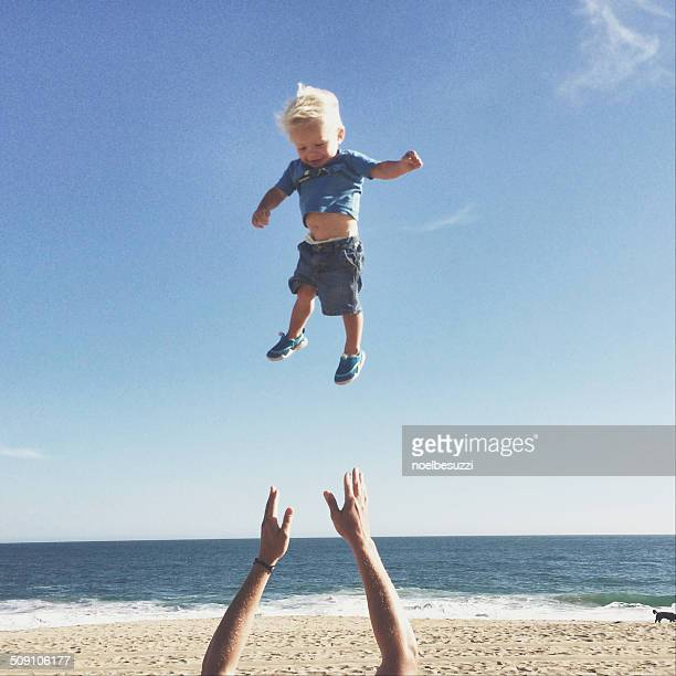 Father throwing son up in air