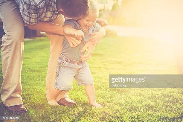 Father tickling his little barefoot boy making him laugh