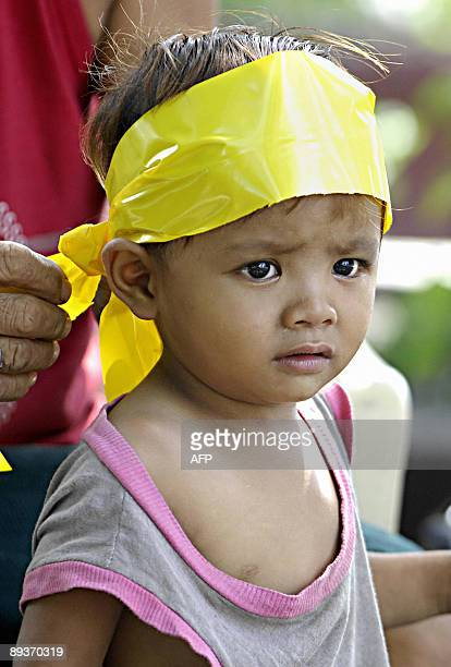 A father ties a yellow ribbon on his son's head as a sign of support for cancer striken former president Corazon Aquino in Manila on July 24 2009 The...