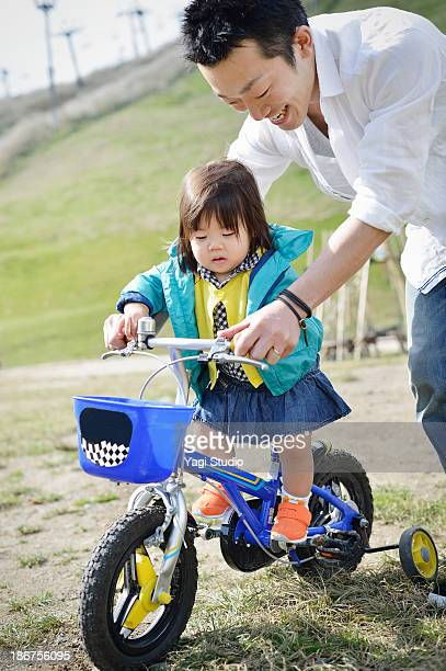 Father to put on the bike the daughter