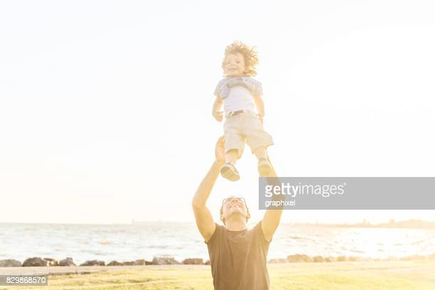 Father tossing son in air