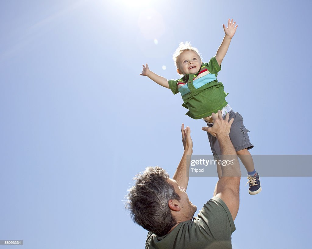Father tossing son in air : Stock Photo