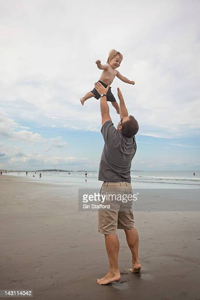 Father tossing young son up in the air at beach