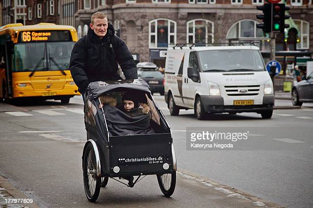 CONTENT] A father transporting his two kids by a tricycle with frontcar in Copenhagen Denmark