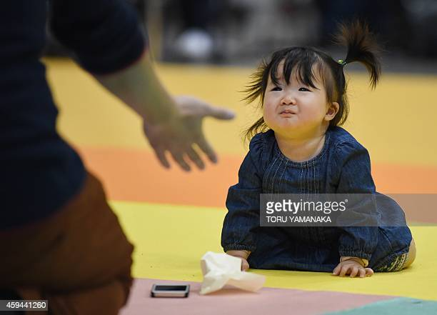 A father tries to coax his baby to the finish line during the Baby Super Crawl Dash at an event for young parents in Yokohama in suburban Tokyo on...
