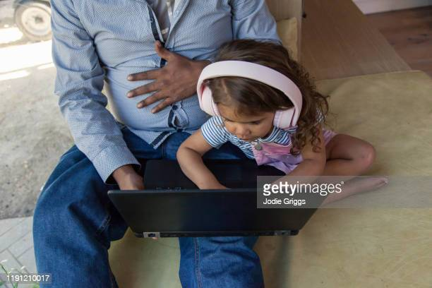 Father trying to use on a laptop at home while young child tries to press the keyboard