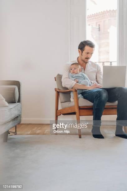 padre tratando de trabajar desde casa - masculinidad moderna fotografías e imágenes de stock