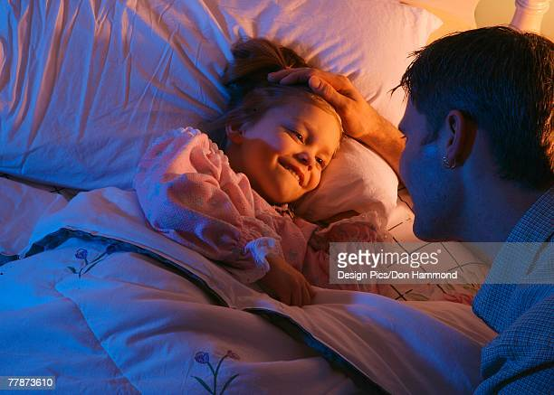 Father tucking daughter into bed