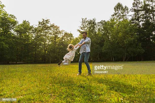 Father turning daughter on meadow