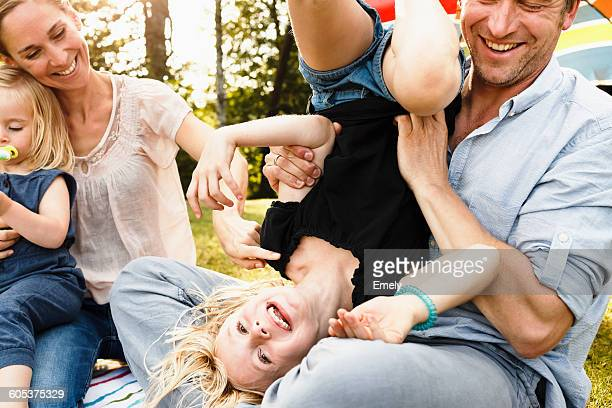 Father turning daughter upside down at family picnic in park