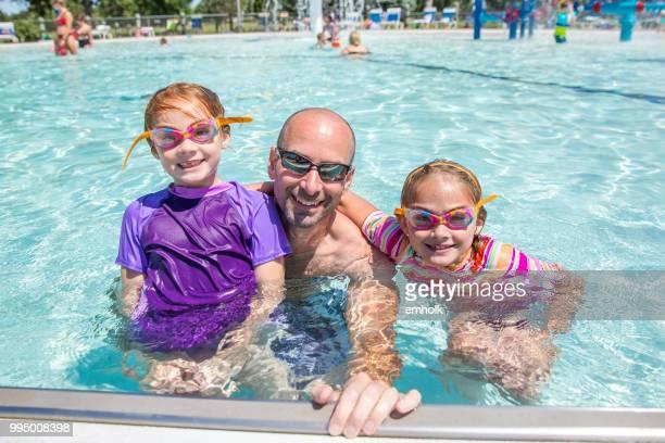 vader & twee jonge dochters bij buitenzwembad - buitenbad stockfoto's en -beelden