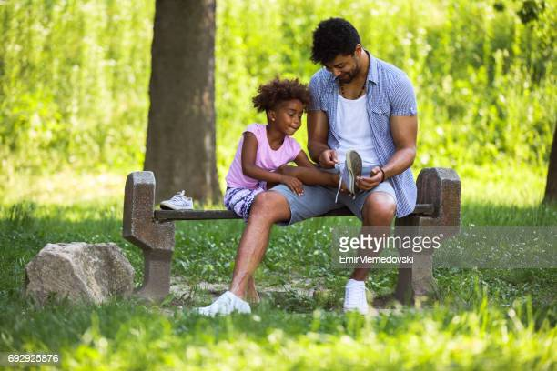 Father tying daughters  shoelaces