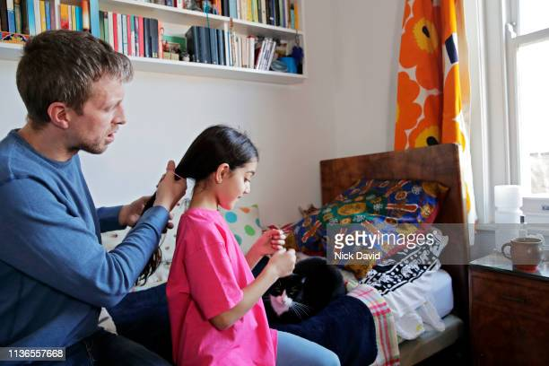 father tying his daughter's hair in a ponytail - single father stock pictures, royalty-free photos & images