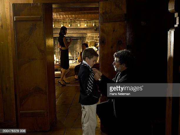 father tying son's (6-8) on tie, women talkingin background - hans neleman ストックフォトと画像
