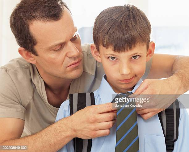 Father tying son's (8-10) tie, portrait of boy, close-up