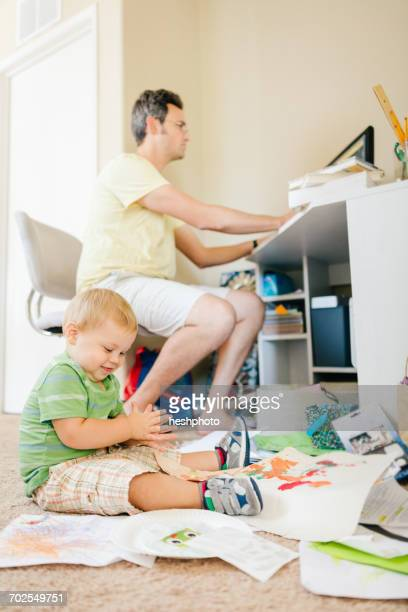 father using computer whilst young son plays on floor - heshphoto stock-fotos und bilder