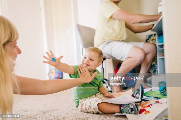 father using computer whilst young son plays on floor with mother - heshphoto photos et images de collection