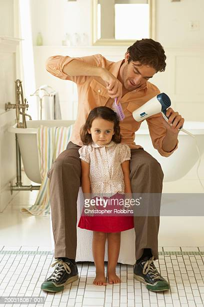 Father using hair dryer on daughter (2-4) in bathroom