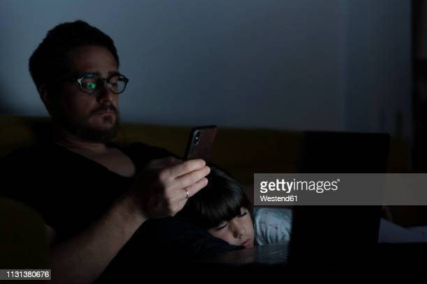 father using laptop and cell phone on couch at night with daughter sleeping - daughters of darkness stock pictures, royalty-free photos & images