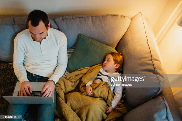 father using laptop in living room while daughter sleeping next to him - next to stock pictures, royalty-free photos & images