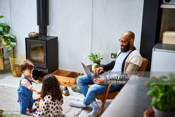 father using laptop with two children in living room - working from home stock pictures, royalty-free photos & images