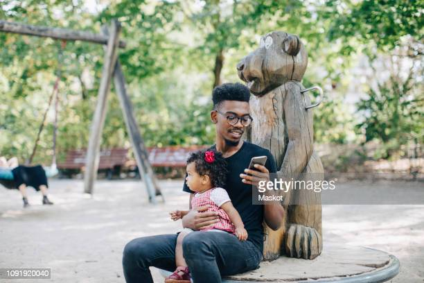 father using mobile phone while sitting with daughter on outdoor play equipment - incidental people stock pictures, royalty-free photos & images
