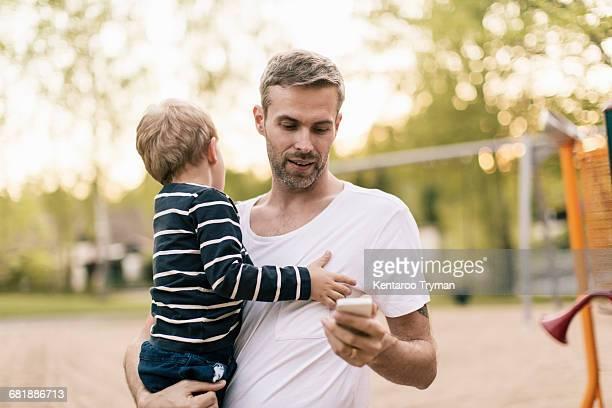 father using phone while carrying son at playground - kinderspielplatz stock-fotos und bilder
