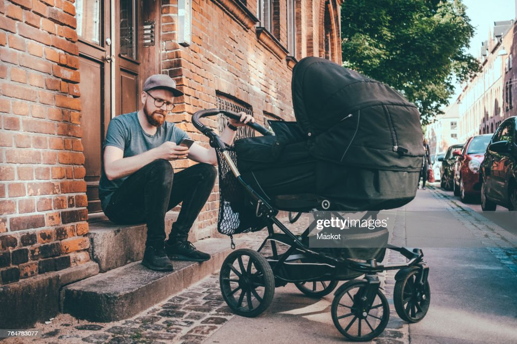 Father using smart phone while holding baby carriage on steps at building entrance : Stock Photo