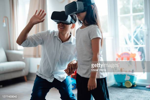 father using virtual reality headset with his daughter - genderblend stock pictures, royalty-free photos & images