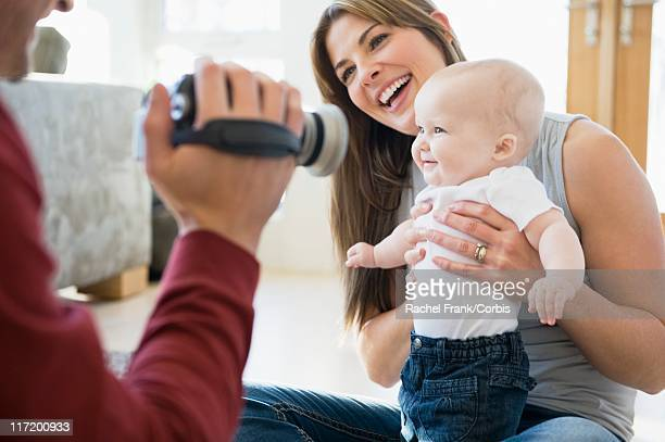 Father video recording baby girl