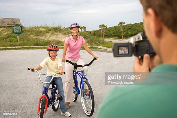 Father videotaping wife and daughter on bikes