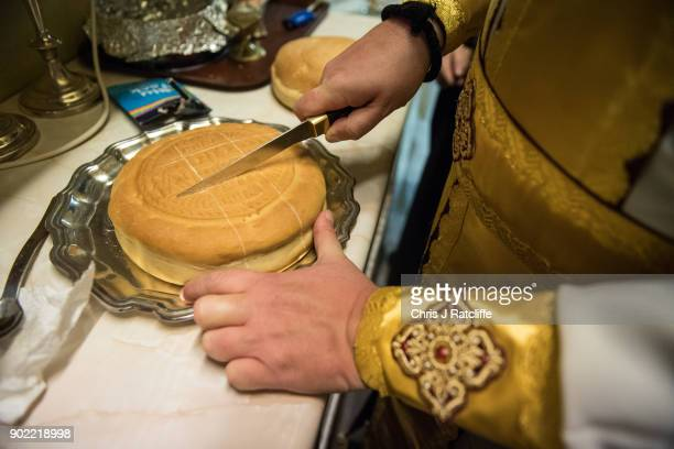 Father Vissarion cuts bread during a traditional Greek Orthodox service at the Church of St Michael the Archangel for the Feast of the Epiphany on...