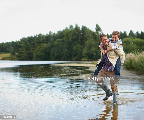 Father wading in lake, giving son piggyback.